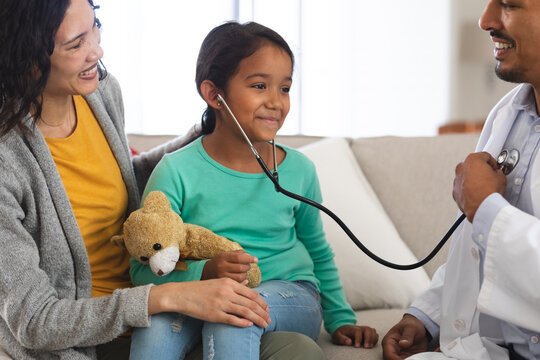 Happy hispanic male doctor and girl patient with mother playing with stethoscope during home visit