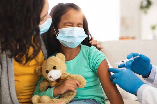 Doctor giving covid vaccination to hispanic girl patient sitting with mother wearing face masks