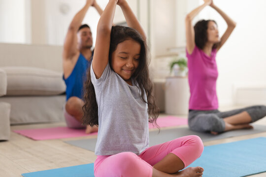 Smiling hispanic daughter and parents practicing yoga sitting in living room