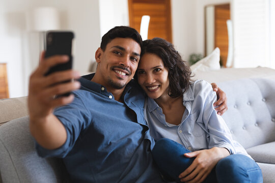 Happy hispanic couple sitting on couch in living room taking selfie and smiling