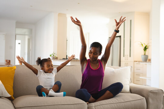 Happy african american mother and daughter practicing yoga, sitting on couch in living room