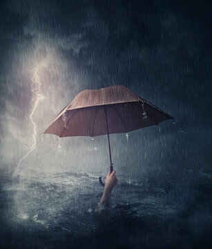 Human hand holding an umbrella sinking in the ocean. Surreal and dramatic scene of person drowning in the sea waters under the storm. Business despair and failure metaphor. Crisis problems concept