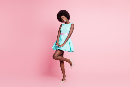 Full size photo of young happy charming positive shy modest afro girl in lovely dress isolated on pink color background