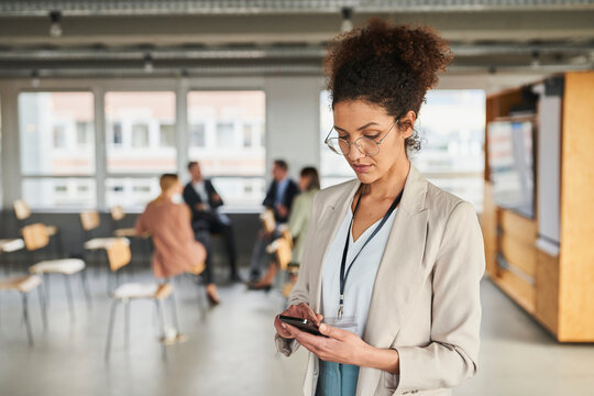Female entrepreneur using mobile phone with colleagues in background at office