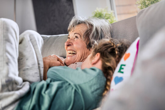 Cheerful grandmother lying by granddaughter on sofa at home