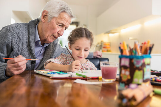 Granddaughter and grandfather painting together at home