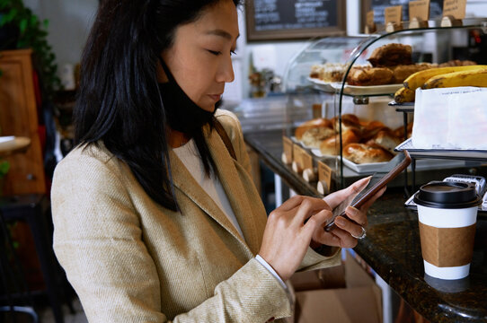 Female customer using smart phone to pay at bakery