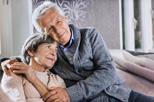 Senior man sitting with arm around on woman in living room