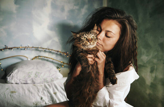 Woman embracing cat while sitting in bedroom