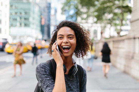 Woman laughing while talking on smart phone in city
