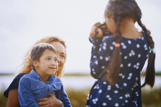 Germany, Girl taking photo of her mother and brother. The boy has Down's syndrome