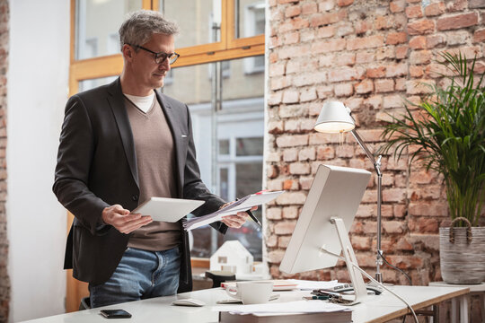 Mature man with digital tablet and paper document working in office