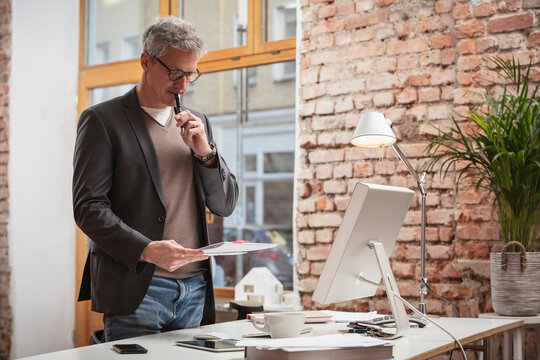 Thoughtful male professional with pen working on paper document by desk at work place