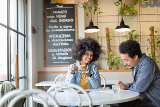 Female professional having coffee while sitting with male customer at cafe