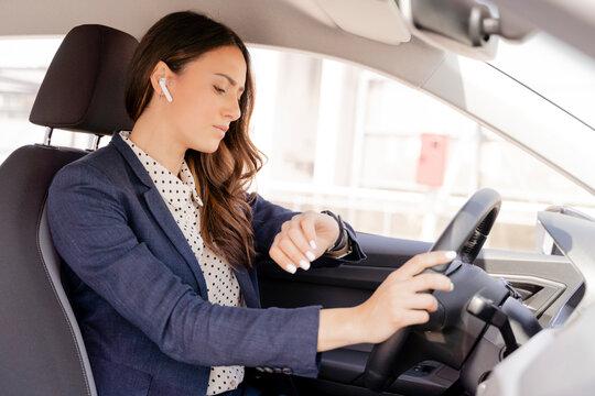 Female entrepreneur checking time while driving car