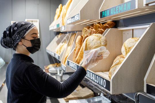 Female baker wearing mask working in bakery
