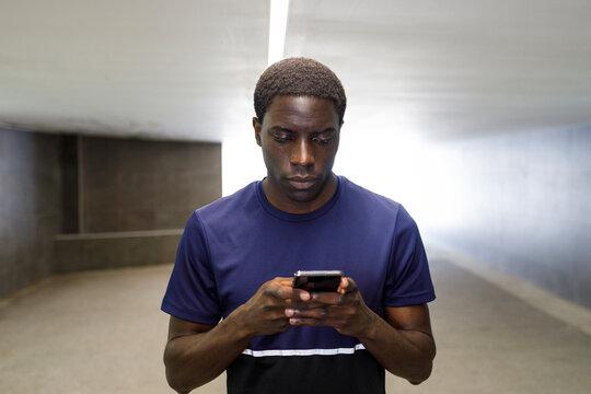 Handsome man text messaging through smart phone in underground