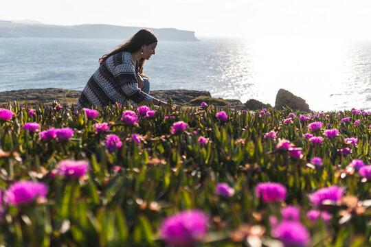 Young woman at carpobrotus edulis field by sea