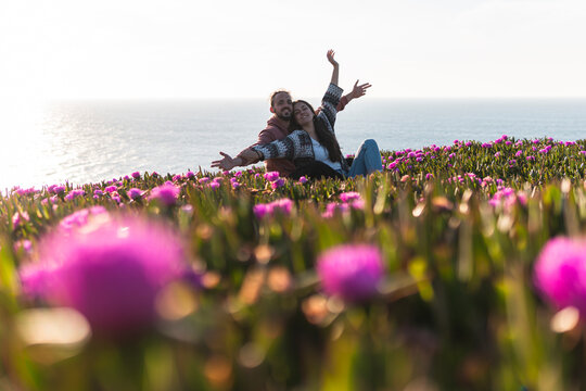 Young couple with arms outstretched sitting at flower filed by sea