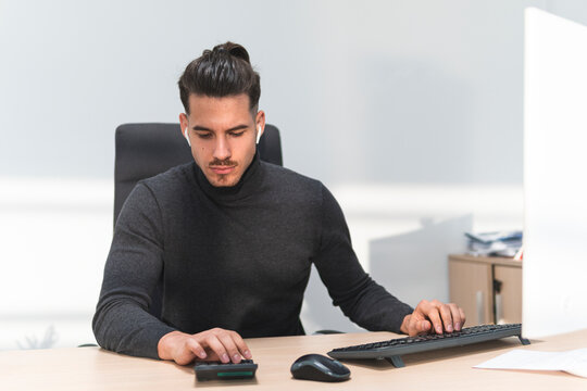 Male financial advisor calculating on calculator by computer at work place