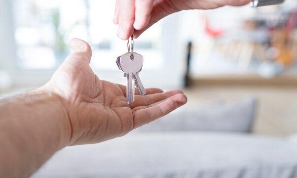 Hand handing over house keys