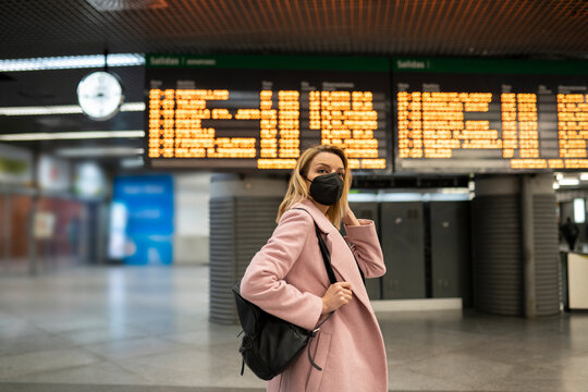 Mid adult woman wearing protective face mask standing on airport