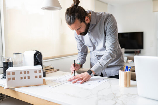 Male architect designing construction plan while working at home