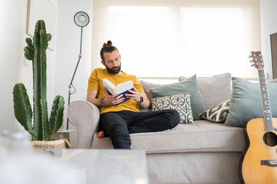 Handsome man reading book while sitting on sofa at home