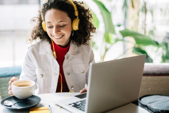 Smiling woman with laptop and headphones having coffee at cafe