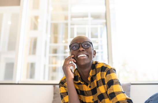 Smiling woman talking on mobile phone at home