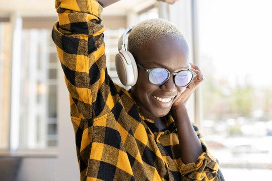 Smiling woman wearing headphones dancing at home