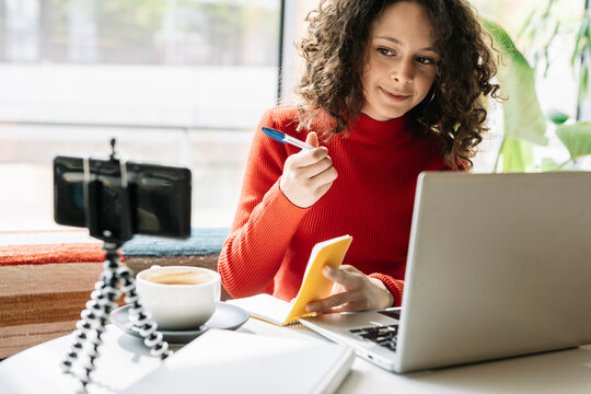 Female influencer with laptop looking in smart phone at cafe
