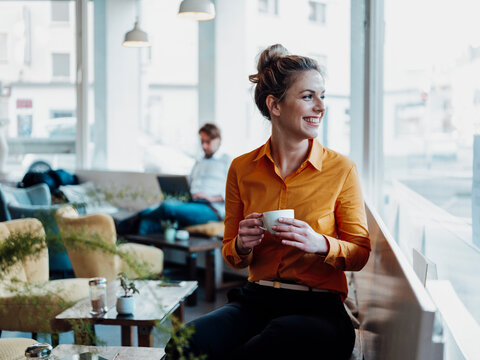 Smiling businesswoman holding coffee cup while sitting with colleague in cafe