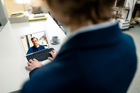 Businesswoman working with colleague on video call through digital tablet in industry