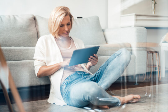Blond hair woman with digital tablet sitting on floor at home