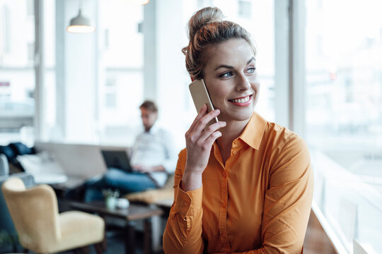 Smiling entrepreneur talking on mobile phone with colleague in background at cafe