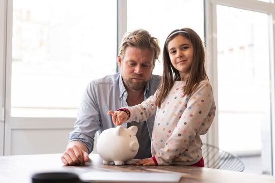 Daughter and father with piggy bank at home