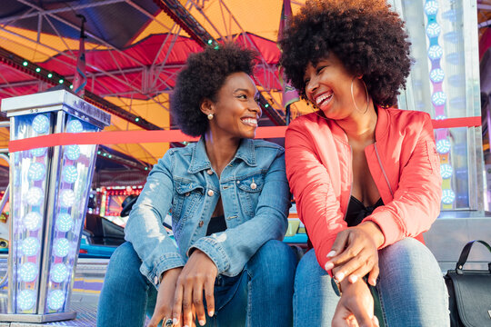 Happy female friends talking with each other while sitting in amusement park