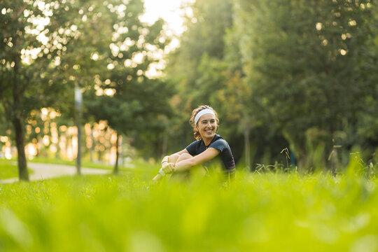 Smiling woman hugging knees while sitting on grass at public park