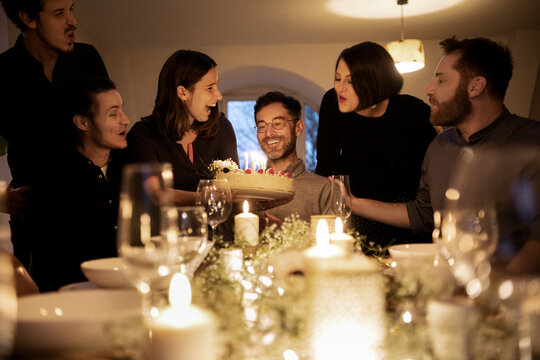 Male and female friends cheering during birthday celebration of smiling man at home