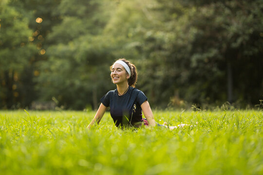 Smiling woman practicing yoga on grass in public park