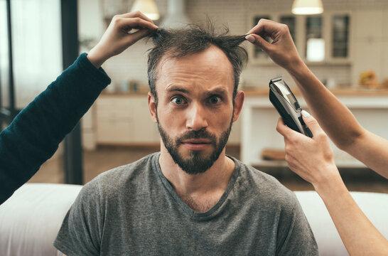 Confused man having haircut at home