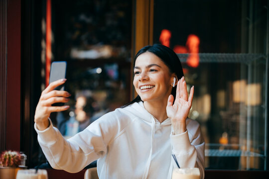 Cheerful woman waving on video call while sitting in cafe
