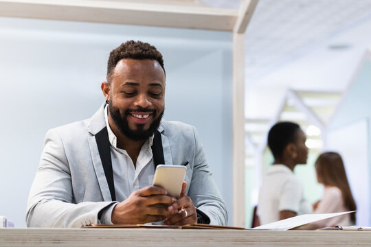 Smiling businessman using mobile phone at office