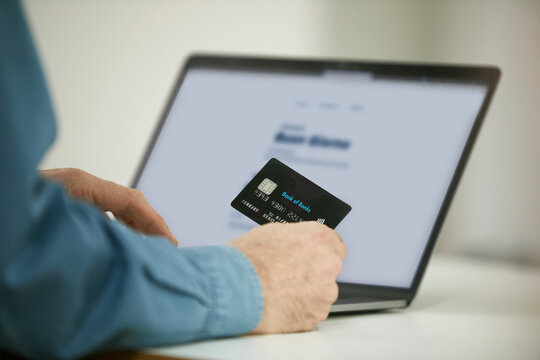 Man using paying through credit card while online shopping on laptop in office