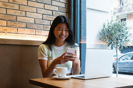 Smiling woman using smart phone by laptop while sitting in cafe