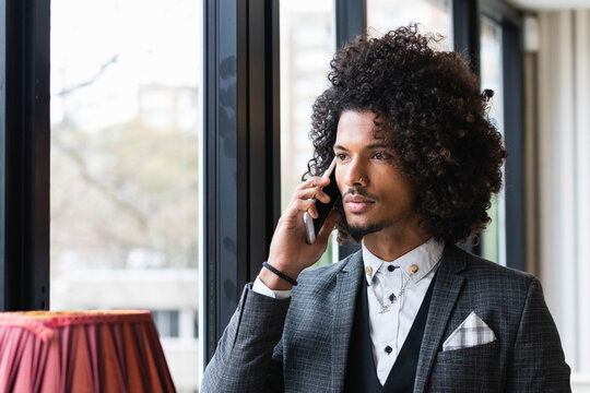 Young male entrepreneur talking through mobile phone in coffee shop