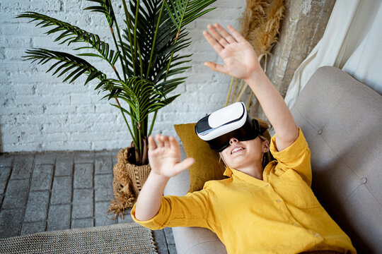 Young woman gesturing wearing Virtual reality simulator while lying on sofa at home