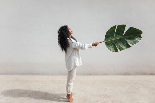Curly haired woman with big banana leaf standing on tiptoes by white wall during sunny day