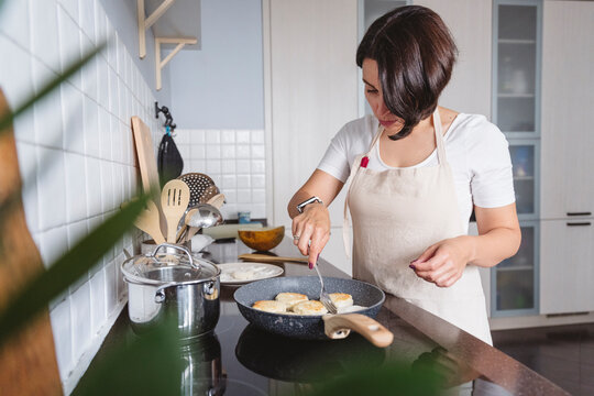 Mid adult woman preparing food in kitchen at home